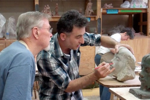 Sculpture instructor George Tkabladze talks with a student in Wood & Stone Sculpture.